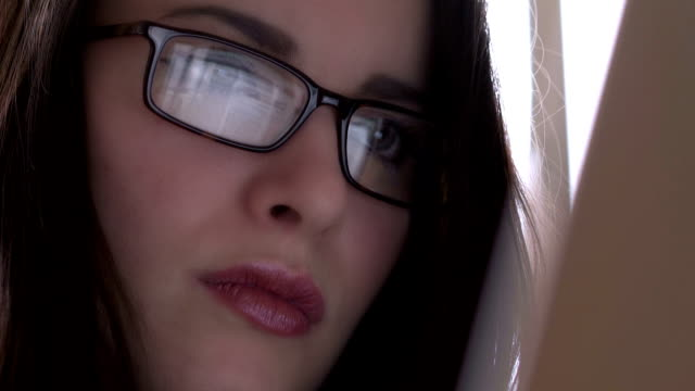 Laptop, glasses reflection. Young woman, close. video