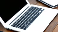 Laptop, mobile phone, notebook and cup of coffee arranged on wooden table video