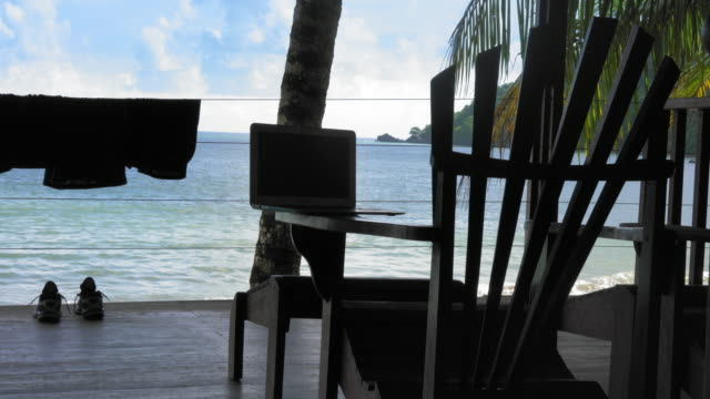 Laptop on Adirondack chair at a tourist resort, Trinidad, Trinidad and Tobago video