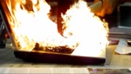 SLO MO Laptop on fire struck by a hammer video
