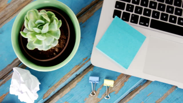 Laptop, sticky notes, pot plant, pencil, crumpled paper and binder clips video