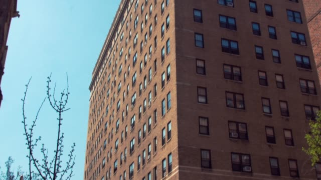 Large brick apartment building and clear summer sky video