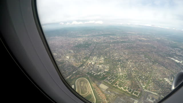 Large city seen through window of plane flying high in sky, air travel service video