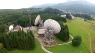 Large dish satellite antennas array receiving and broadcasting data signal over mountain area landscape, aerial view video