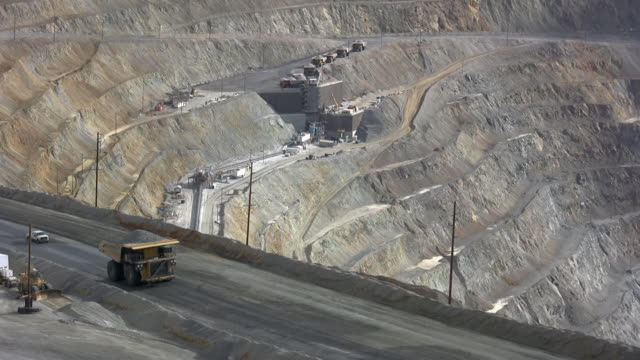 Large dump truck hauling iron ore in a mine video