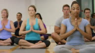 Large Fitness Class Sits in Prayer Pose video