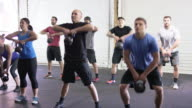 Large group class doing a kettlebell workout together in an industrial gym video