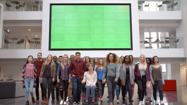 Large group of students walk to camera in university atrium video