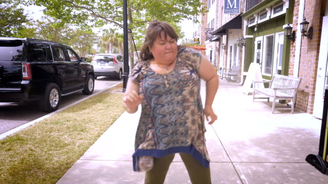 A large happy woman dancing and moving her arms around outside video
