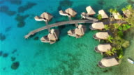 AERIAL: Large luxurious overwater villas nestled in the turquoise blue lagoon, with lush tropical landscapes and white sandy beaches in luxury hotel resort on a beautiful sunny tropical island. Perfect romantic getaway video