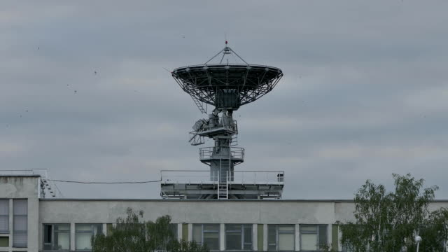 Large Nine-Meter Dish-Shaped Antenna on Roof of Govermental Research Institute in Minsk, Belarus Waits for Satellite Signals From Space Against Sky With Clouds and Birds video
