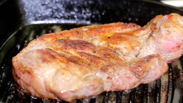 Large piece of fresh beef meat prepared on a grill pan. Toned. hot steak on grill pan video