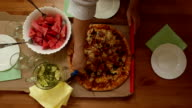 Large pizza divided by disc cutter, view from top, wooden table. video