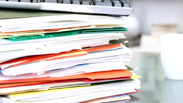 Large stack of files, documents, paperwork on desk. video