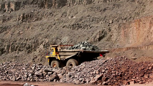 A large tipper digs through a career, an industrial truck dredges cargo in its quarry, a large yellow dumper video