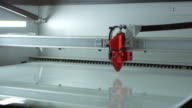 A laser cutter in operation at a 3D printing lab, shot on R3D video