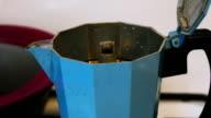 Last Drops of Italian coffee sprinkling out of blue moka coffee-pot macro shot video