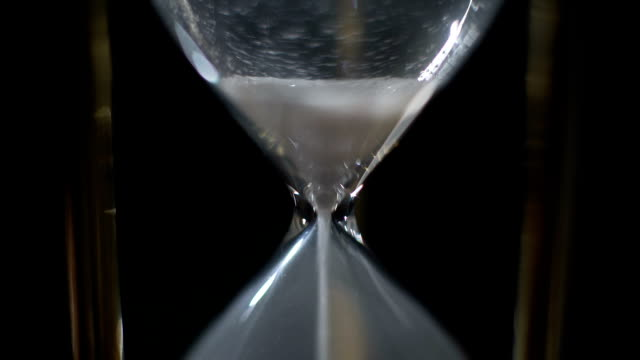 Last grains of sand falling in hourglass, time running out, end of life, closeup video
