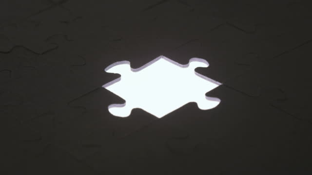 Last piece of jigsaw puzzle with silhouette light video