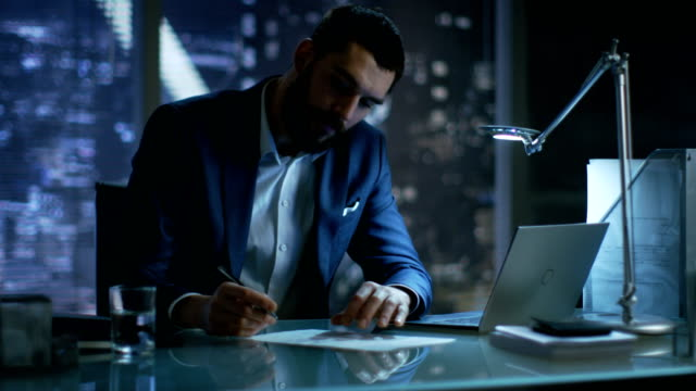 Late at Night Businessman Works on a Laptop and Signs Documents in His Private Office with Big City Window View. video
