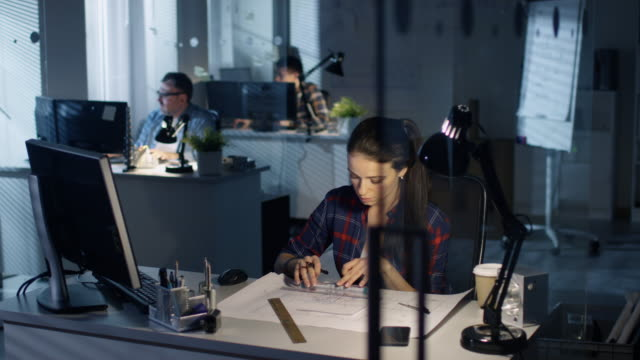Late at Night Female Design Engineer Uses Computer, Works on Her Drafts with Engineer's Scale Ruler. She's Sitting at Her Desk. Lamp Illuminates Her Table. Colleagues Work in the Background. video