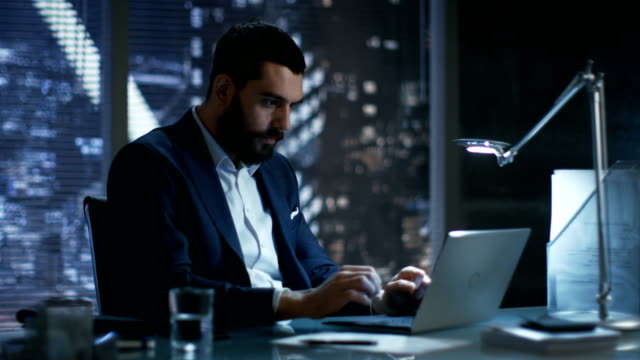 Late at Night in Private Office Businessman Works on a Laptop. He Succeeded Internationally by Winning Big Contract. He's Very Happy. video