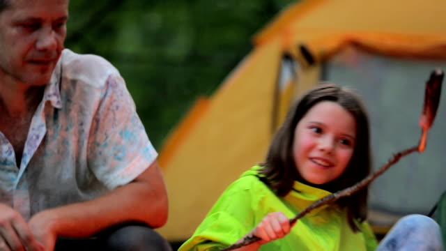 Late evening in camp, father and daughter sitting by the fire video