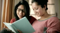 Late teen happy girl students studying book together. video