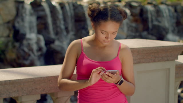 Latin girl using smartphone at park. African woman using phone outdoor video