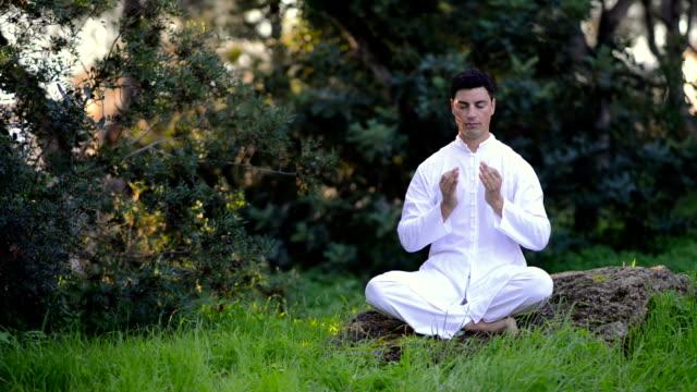 latin man meditating in a green park video