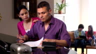 Latin Parents Discuss Home Finances with Kids in Background video