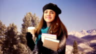 Latin student with books, disposable coffee cup in winter snow. video