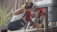 Latina Carpenter Drilling Plank In Her Workshop video