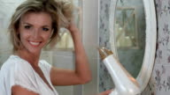 Laughing beautiful woman dries her hair with hairdryer video