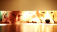 Laughing  boy with his best friend beagle dog under bed video