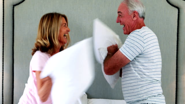 Laughing couple having pillow fight on bed video