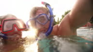 Laughing couple in pool wearing snorkelling gear with lens flare video