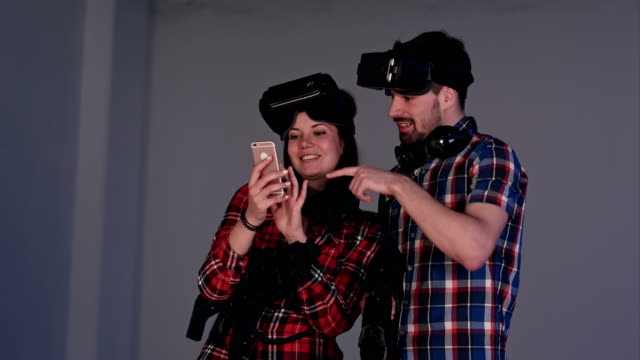 Laughing couple in virtual reality headsets looking at their funny photos on the phone video