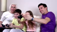 Laughing family playing video games in a living room video