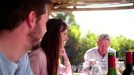 laughing Woman at a table during a family dinner video