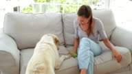 Laughing woman playing with her labrador dog on the couch video