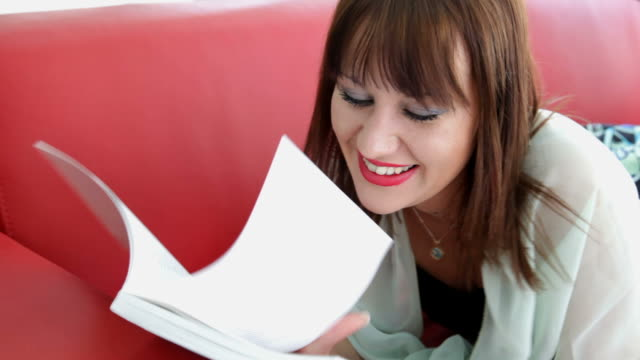 Laughing woman with a book lies on red sofa video