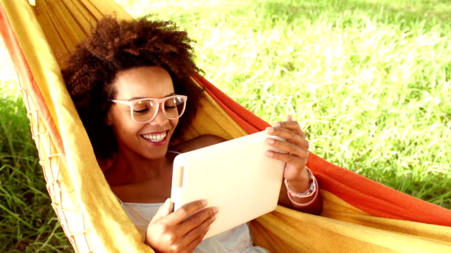 laughing young woman in a hammock looking at digital tablet video