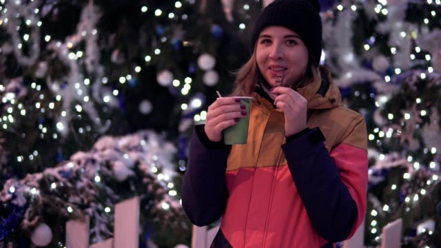 Laughing young woman with hot tea and peace of chocolate near christmas tree. Accomplishment of desires concept video