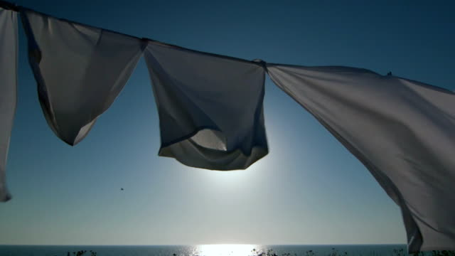 Laundry drying on clothesline against blue sky and sun video