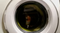 Laundry machine spinning in fast mode, drying textile, brainwash video