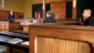 Lawyer questions witness in Courthouse - Two shots video