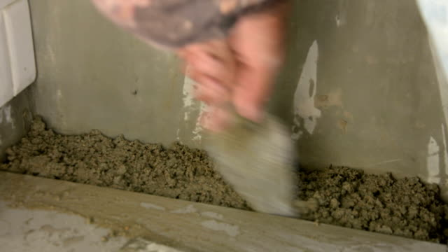 laying ceramic wood tiles on floor, installing tiles  in construction site. video