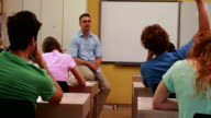 Lecturer sitting and speaking to his students in classroom video