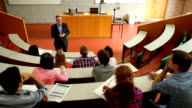 Lecturer speaking to his class in the lecture hall video
